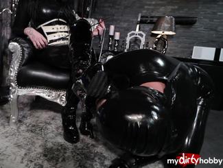 Miss Lana Poison sitzt in ihrem hautengen, schwarz-glänzenden Latexcatsuit entspannt auf ihrem Thron, während ihr untergebener vollgummierter Latexsklave nach Anweisungen der Herrin die schwarz-glänzenden Lack-Overkneestiefel mit seiner lustvollen Sklavenzunge sauberleckt